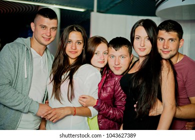 Odessa, Ukraine August 22, 2015: People smiling and posing on cam during concert in night club party. Man and woman have fun at club. Boy and girl at night club party