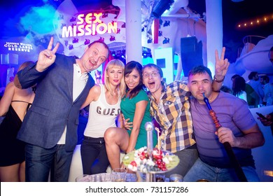 Odessa, Ukraine August 24, 2014: Ibiza night club. People smiling and posing on cam during concert in night club party. Man and woman have fun at club. Boy and girl at night club party