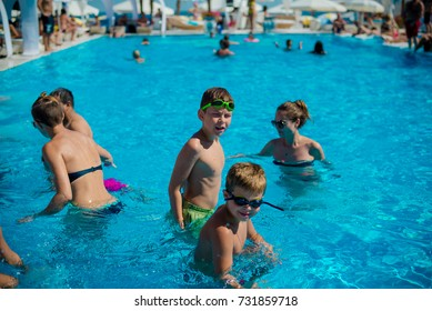 Odessa, Ukraine August 24, 2015: Pool party at summer club during holidays time. Enjoying pool party with friends. Group of young people looking happy while jumping into the swimming pool together.