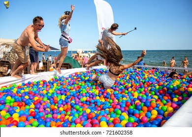 ODESSA, UKRAINE - AUGUST 24, 2017: Young people, athletes entertain themselves by doing acrobatic jumps in pool with colorful colorful plastic balls. Swimming pool. multi-colored plastic balls