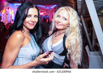 Odessa, Ukraine August 25, 2012: Maxim magazine party with many models in club. People make selfy, drink alcohol, dancing, smiling, smoking hookah and kissing during concert in night club party.