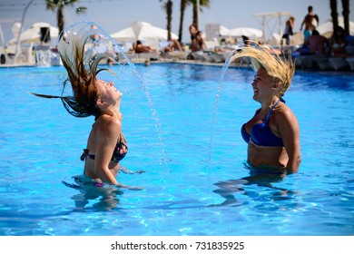 Odessa, Ukraine August 25, 2014: Ibiza club. Beautiful girl in bikini posing on cam during day pool party at summer holidays time. Woman rest in luxury beachfront complex of Ibiza. Day lounge party.