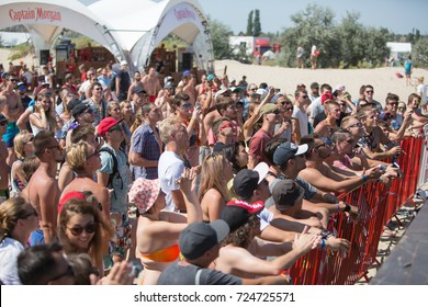 Odessa, Ukraine August 26, 2017: Summer beach concert. People dancing at beach party. large crowd of spectators during day music show. Spectators in sand of beach during rock concert music festival