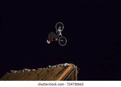 Odessa, Ukraine August 26, 2017: Extreme bike rider jumping. BMX rider making night bike jump during the BMX Competition. Night Dirt