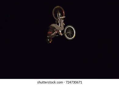Odessa, Ukraine August 26, 2017: Extreme bike rider jumping. BMX rider making night bike jump during the BMX Competition. Night Dirt