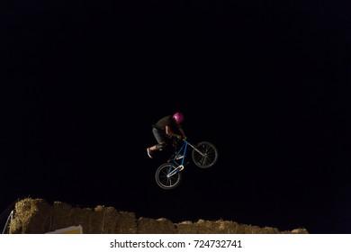 Odessa, Ukraine August 26, 2017: Extreme bike rider jumping. Unidentified BMX rider making night bike jump during the BMX Competition. Night Dirt