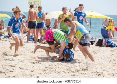 Odessa, Ukraine August 27, 2017: International Rugby Festival on sand of sea beach during sports open air festival. Rugby players men and women in action on beach sand. Rugby. Friends playing rugby