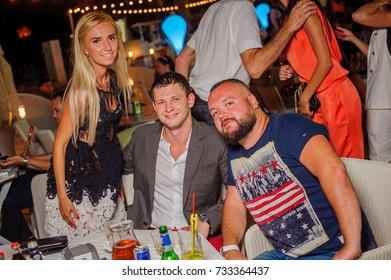 Odessa, Ukraine August 29, 2015: Ibiza club. People smiling and posing on cam during concert in night club party. Man and woman have fun at club. Boy and girl at night club party
