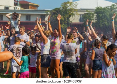ODESSA, UKRAINE - August 5, 2017: Young people, boys and girls are having fun during the Holi holiday, throwing colorful powder at each other. Boys and girls in wet clothes have fun. Wet party