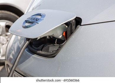 Odessa, Ukraine - August 5, 2017: The Nissan Leaf  charging an electric car with the power cable supply plugged in,  close up.