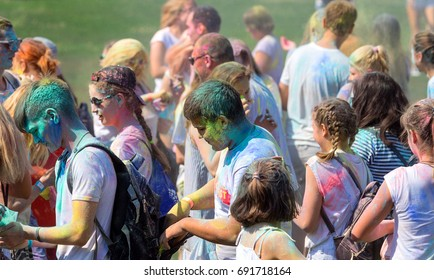 ODESSA, UKRAINE - August 5, 2017: Young people, boys and girls have fun during Holi holiday, throwing colorful powder into each other. Festival of Colored Paint. festival of colors love. Color fest