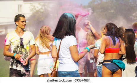 ODESSA, UKRAINE - August 5, 2017: Young people, boys and girls have fun during Holi holiday, throwing colorful powder into each other. Festival of Colored Paint, of colors, love. Color fest