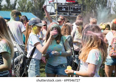 Odessa, Ukraine August 5, 2017: Young people celebrate Holi color festival in park. Happy friends partying with colorful powder cloud at holi festival in summer time. Holi festival of color