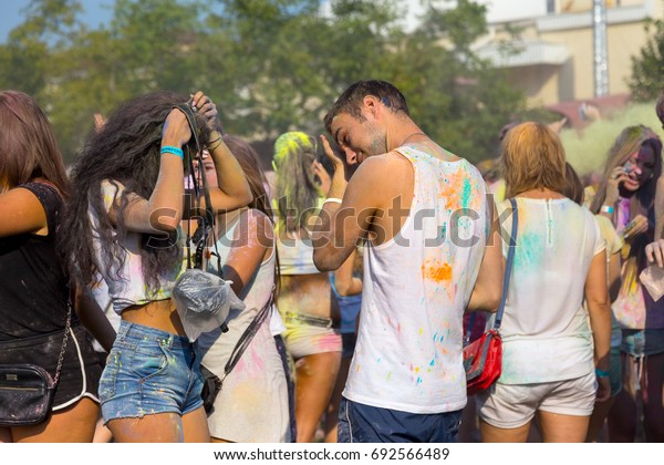ODESSA, UKRAINE - August 5, 2017: Young people, boys and girls have fun doing selfie during festival of Holi by throwing coloured powder at each other. Festival of Colored Paint, colors. Color fest