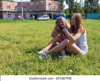 ODESSA, UKRAINE - August 5, 2017:Two girls sprinkled each other with colored powders, sit and relax on the green lawn during the festival of Holi. Festival of Colored Paint, of colors love. Color fest