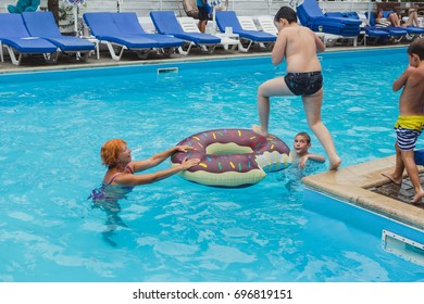 Odessa, Ukraine August 6, 2017: Pool party at summer club during holidays time. Enjoying pool party with friends. Group of beautiful young people looking happy while jumping into the swimming pool.