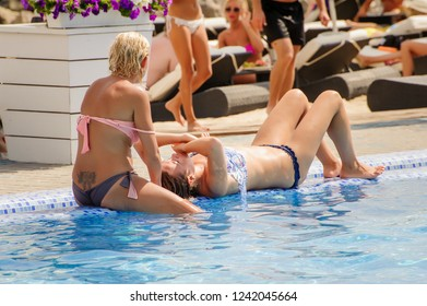 Odessa, Ukraine August 7, 2016: Privat Elling beach club Beautiful girl in bikini posing on cam during day pool party at summer holidays time. Woman rest in luxury beachfront complex. Day lounge party
