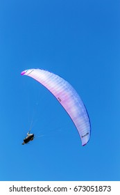 ODESSA, UKRAINE - CIRCA 2017:  beautiful hang-glider hangs in air above a steep mountain slope. Wing hang glider with pilot in blue sky on sunny summer day. Extreme sports aeronautics