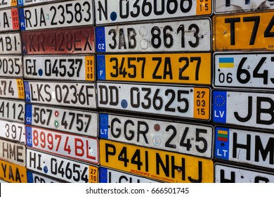 ODESSA, UKRAINE- CIRCA 2017: Discontinued license car numbers from Europe cars on old wall. Mosaic from old retro antique car plates of Europe. Interrupted license numbers from around world on display
