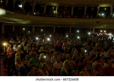 ODESSA, UKRAINE - CIRCA 2017: Large crowd of spectators with pleasure at concert in theater. Spectators in theater during popular concert shine with flashlights of phones in support of popular singer