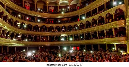 ODESSA, UKRAINE - CIRCA 2017: Large crowd of spectators with pleasure at concert in theater. Spectators in theater during popular concert shine with flashlights of phones in support of popular singer