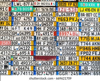 Odessa, Ukraine - circa 2017: License numbers auto from all over world on display. Discontinued license plate of cars from Europe car on wall. Background of vintage antique car license plates Europe.