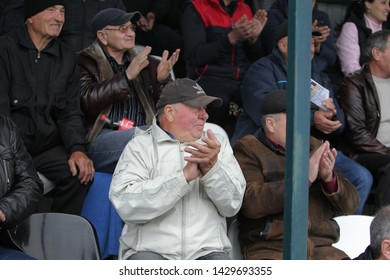 ODESSA, UKRAINE - CIRCA 2019: Crowds of fans in the stands of a football stadium during a match of regional clubs. Spectators at the stadium. Stands with fans on football