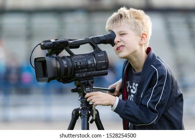 ODESSA, UKRAINE - CIRCA 2019: A little boy, a teenager, shoots 4K video on a professional video camera on the green field of the stadium. Young videographer with a television camera