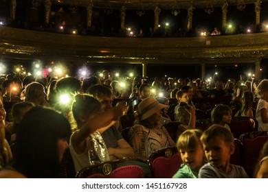 Odessa, Ukraine - CIRCA 2019: selective focus. Spectators children in theater during popular children's play. Children's Delight audience. Concert audience in motion. Children's spectators in theater