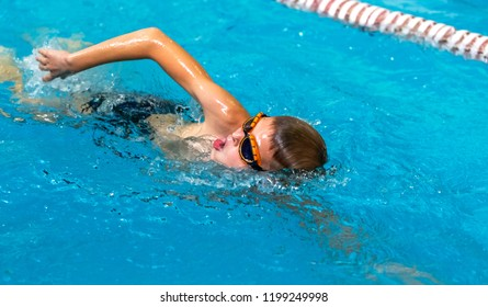 ODESSA, UKRAINE - CIRKA 2016: Children, athletes, swimmers swim along tracks in sports pool for swimming. Sports swimming in pool. Summer Olympic sport, healthy lifestyle, children's sport
