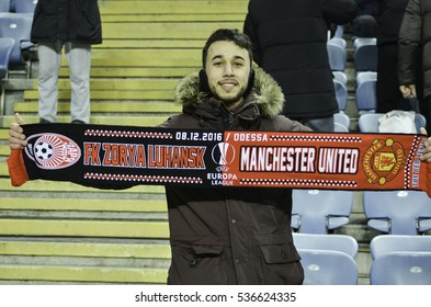 ODESSA, UKRAINE - December 08, 2016: Active fans in the stadium with the attributes of Manchester United during the UEFA Europa League match between Zarya Lugansk vs Manchester United,  Ukraine