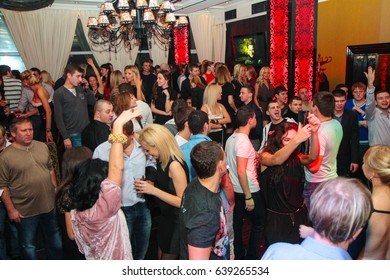 Odessa, Ukraine December 10, 2011: Night club dj party people enjoy of music dancing sound with colorful light with Smoke Machine and lights show. Hands up in the earth.