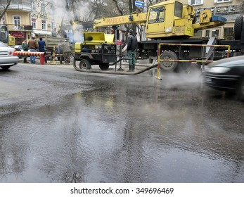 Odessa, Ukraine  -  December 10, 2015: Emergency workers repair the main heat pipes. Outside the overcast and cold, hot water is poured on the road in the city center.
