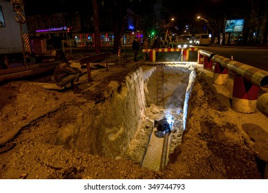 Odessa, Ukraine - December 10, 2015:workers doing emergency repairs urban highways engineering at night. Repair and replacement of water, sewer pipes during night at  bottom of deep trench. Accident.