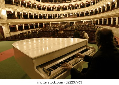 Odessa, Ukraine - December 11, 2012: The interior of the opera house after restoration. Spectators filled the place to the festive gala concert. A musician on the piano fills pause expectations
