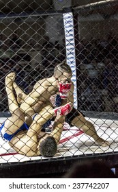Odessa, Ukraine - December 13: Athletics MMA mixed martial arts fighters compete in the cell, causing punches and kicks. Dramatic moment of battle, December 13, 2014 in Odessa, Ukraine