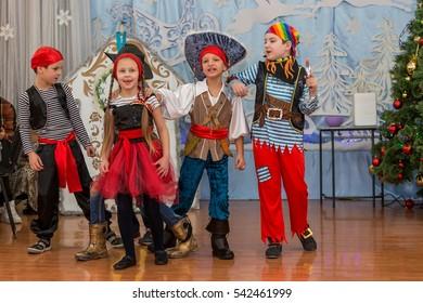 Odessa, Ukraine - December 22, 2016: Children's Christmas New Year's concert. Children play with Snow Maiden and Santa Claus. Emotional bright children's show in elementary school