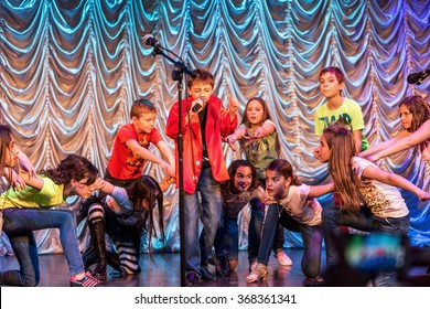 Odessa, Ukraine - December 24, 2015: Children's musical groups singing and dancing on stage in bright colorful clothes. Emotional, touching children's musical stage show.