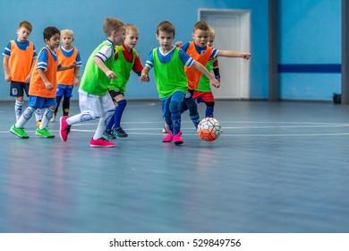 Odessa, Ukraine - December 3, 2016: Little boys, children play in mini-football in indoor sports hall at Junior championship sports city. Children sports - healthy lifestyle. Sport boy footballers.
