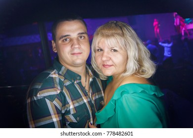 Odessa, Ukraine December 7, 2016: People smiling and posing on cam during concert in night club party. Man and woman have fun at club. Boy and girl at night club party