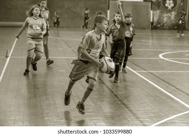 ODESSA, UKRAINE- Febr 24,2018: Young children play rugby during derby games of city school in closed hall. Children's sports. Children play in rugby 5. Fight for victory of children. Healthy lifestyle