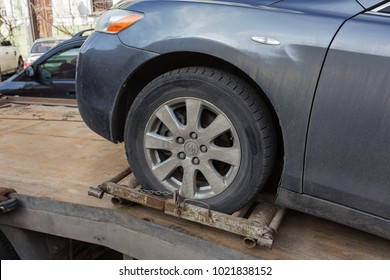 ODESSA, UKRAINE - February 10, 2018: Traffic police officers take towed car on tow truck. car is loaded into the tow, onto platform of tow truck. Emergency towing of a car on a forklift truck
