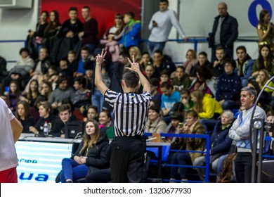 Odessa, Ukraine - February 16, 2019: A sports basketball referee oversees the battle of basketball players on the court during a game. Special gestures and signs of the basketball referee during game
