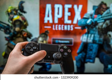 Odessa, Ukraine - February 19, 2019. Black playstation 4 gamepad on the background of the game APEX Legends from EA Games. Apex Legends free to play Battle Royale shooting game.