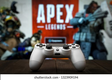 Odessa, Ukraine - February 24, 2019. Black playstation 4 gamepad on the background of the game APEX Legends from EA Games. Apex Legends free to play Battle Royale shooting game.