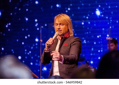 ODESSA, UKRAINE - January 1, 2017: Ukrainian popular singer and musician OLEGG Vinnik performing on stage of restaurant, surrounded by admirers, fans on New Year's party. Singer actor on stage