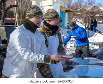 Odessa, Ukraine - January 19, 2016: Ukrainian Army is preparing a meal in the kitchen of field and feeds the military buckwheat freezing rescuers and the homeless on the street during heavy frosts.