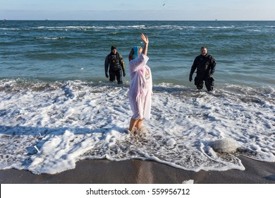 Odessa, Ukraine - January 19, 2017: Orthodox Christians celebrate Baptism of traditional dip in sea of ice water. Epiphany winter Black Sea coast, swimming in freezing water on Epiphany Day