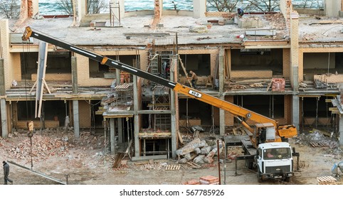 Odessa, Ukraine - January 30, 2017: Workers use manual labor and heavy construction equipment for dismantling and demolition of illegally constructed luxury cottages in recreational marine area beach
