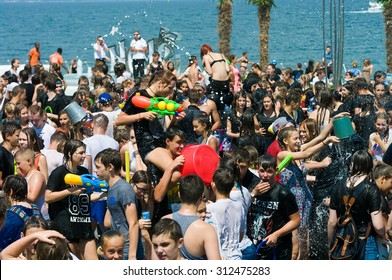 """Odessa, Ukraine - July 1, 2015: young people shooting and throwing water at each other during a flash mob """"Water battle 'on the promenade beach Langeron. Young people having fun and relaxing summer."""